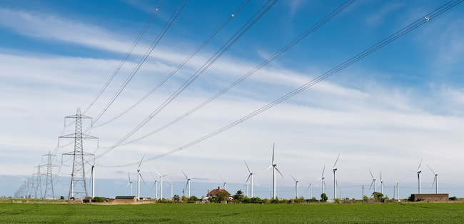 Power lines and wind turbines in East Sussex, UK. Wikipedia Commons Photo by DAVID ILIFF [License: CC-BY-SA 3.0]