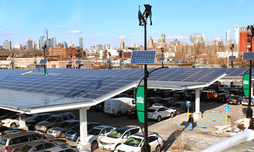 "A ""solar carport"" at a whole foods business in Brooklyn, USA, featuring electric vehicle chargers, wind turbines and solar panels. PHOTO: Urban Green Energy/Ecowatch"