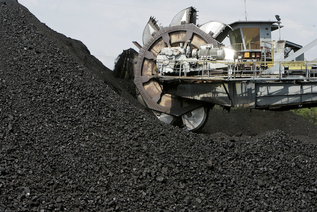 A giant scoop lifts coal on to a conveyor belt at an open pit coal mine. PHOTO Bloomberg